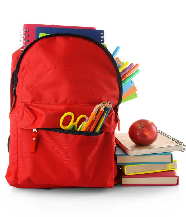 Red Backback with school supplies stickout, next to stack of books, isolated on white